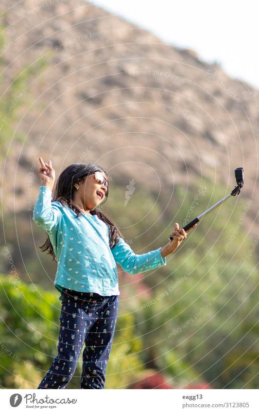 Kleines Mädchen macht ein Foto mit einer Action-Kamera. Lifestyle Freude Glück Leben Freizeit & Hobby Spielen Ferien & Urlaub & Reisen Kind Fotokamera Werkzeug