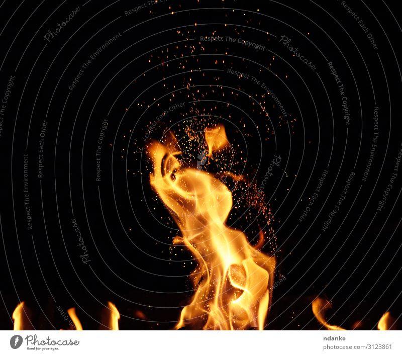 großes brennendes Lagerfeuer mit Flamme und orangenen Funken Design schön Wärme Bewegung fliegen dunkel heiß hell gelb rot schwarz Energie Farbe Hintergrund