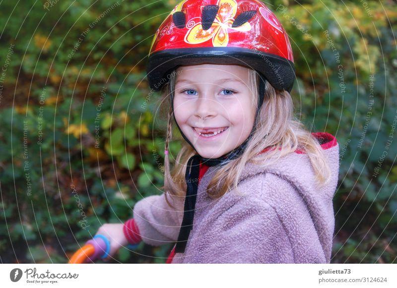 Mit Sicherheit mehr Spaß | Mädchen mit Zahnlücke und Fahrradhelm Spielen Kindheit 1 Mensch 3-8 Jahre Herbst Park Laufrad Helm blond langhaarig Lächeln lachen