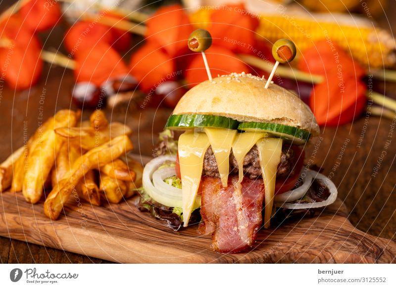 Monster-Burger für Halloween Foodfotografie Lebensmittel Herbst lustig einzeln bedrohlich lecker Gemüse rustikal Schneidebrett Brötchen Gurke Oliven Hamburger