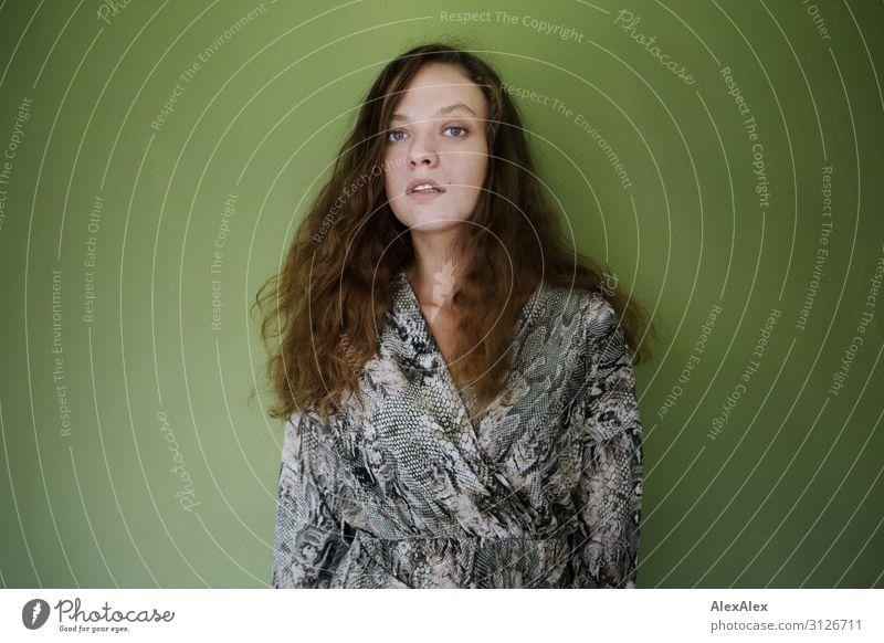 Portrait einer jungen Frau vor grüner Wand Stil schön Leben Wohlgefühl Junge Frau Jugendliche 18-30 Jahre Erwachsene Kleid brünett langhaarig Locken beobachten