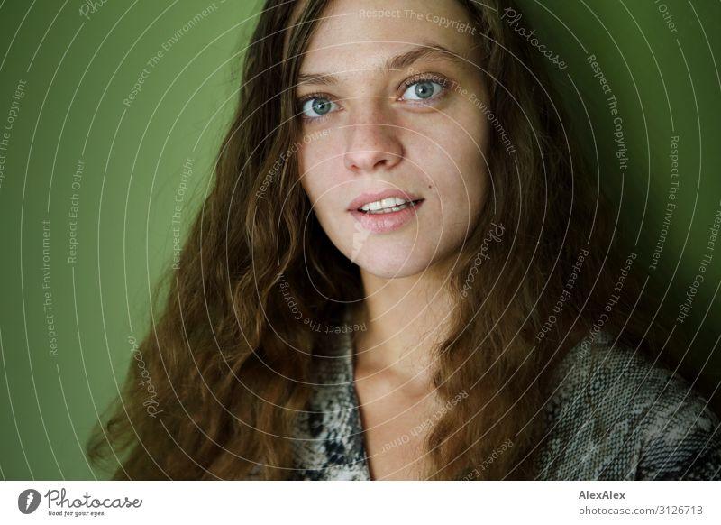 Portrait einer jungen Frau vor grüner Wand Stil Freude schön Wellness Leben Junge Frau Jugendliche 18-30 Jahre Erwachsene brünett langhaarig beobachten Blick