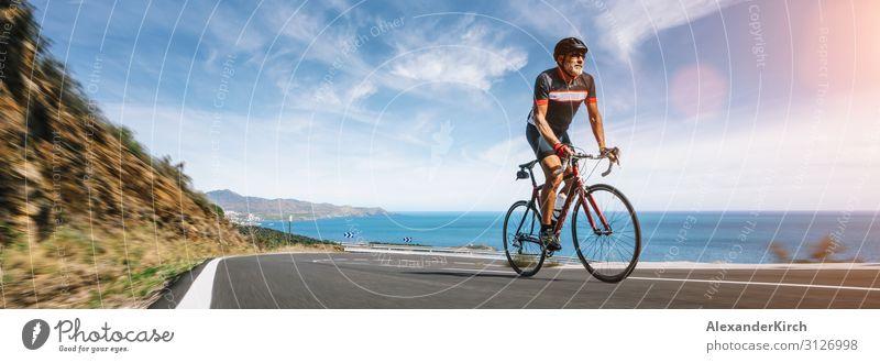 Mature Adult on a racing bike climbing the hill coastal road Mensch Ferien & Urlaub & Reisen Natur Sommer Strand Sport Fitness Sport-Training Autobahn extrem