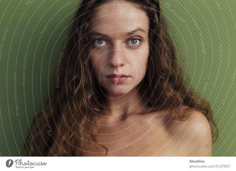 Portrait einer jungen Frau vor grüner Wand Stil schön Wellness Leben Junge Frau Jugendliche 18-30 Jahre Erwachsene brünett langhaarig Locken beobachten Blick
