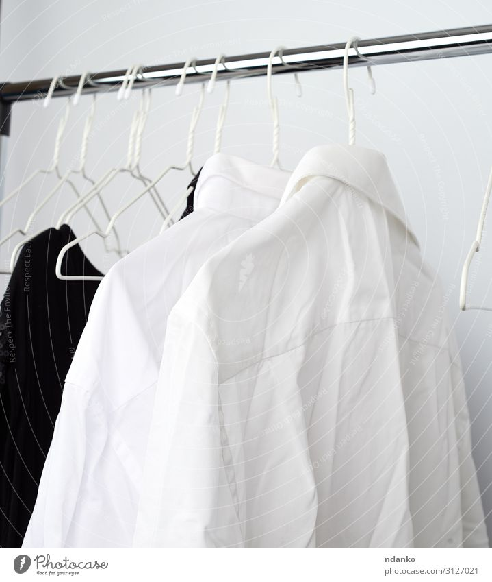 weiße Herrenknitterhemden, die an einem Metallbügel hängen. kaufen maskulin Mode Bekleidung Hemd Kleid Stoff Sauberkeit heimwärts viele knittern Dienst anhaben