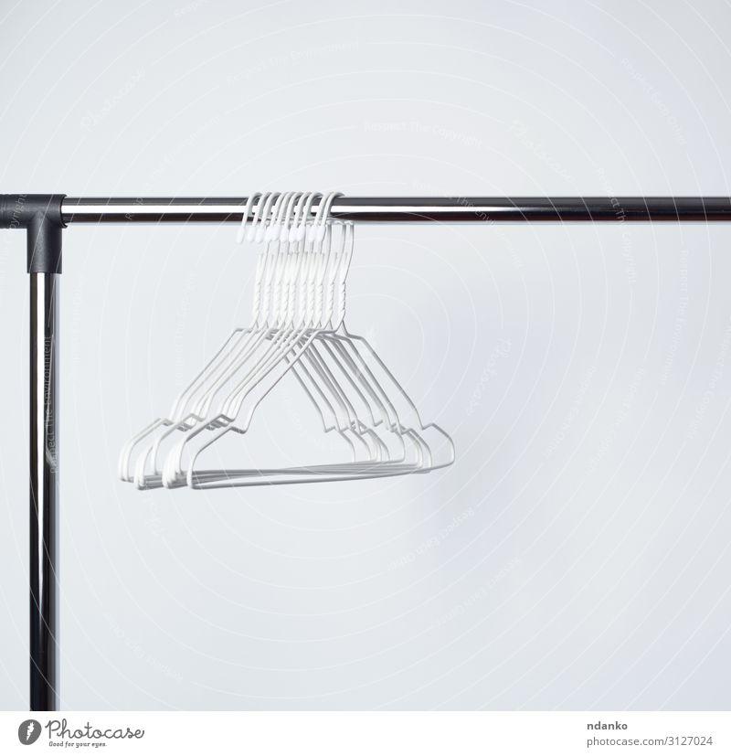 leere weiße Metallbügel hängen an einer Chromstange. kaufen Mode Bekleidung Hemd Stoff Accessoire stehen Hintergrund Lager Schrank Ablage Boutique anhaben