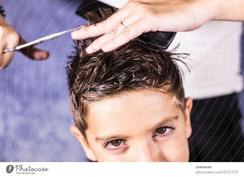 Der schöne Junge lässt sich mit der Schere die Haare schneiden. Lifestyle Stil Körperpflege Haare & Frisuren Kinderzimmer Arbeit & Erwerbstätigkeit Beruf