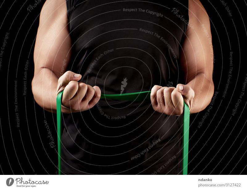 Athlet mit einem muskulösen Körper in schwarzer Kleidung Lifestyle sportlich Fitness Sport Sportler Mensch Mann Erwachsene Arme Hand Band stark grün Kraft