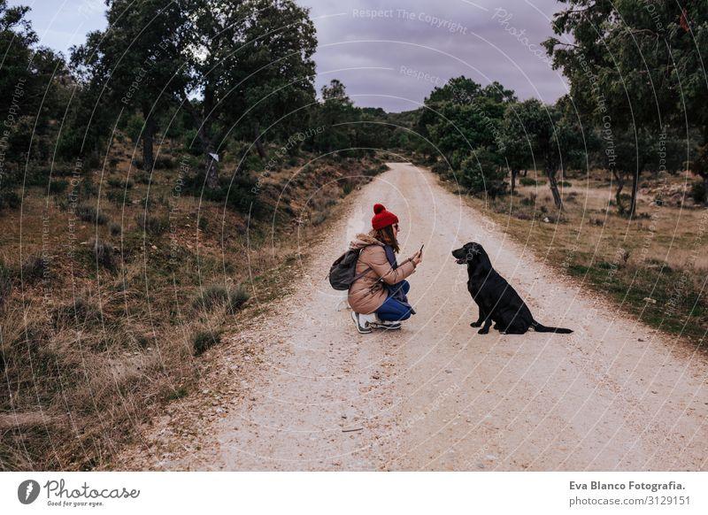 Frau, die draußen in der Natur mit dem Handy telefoniert. außerdem schöner schwarzer Labrador. Unbekümmertheit gehorsam Jugendliche Glück Zunge grün Fürsorge
