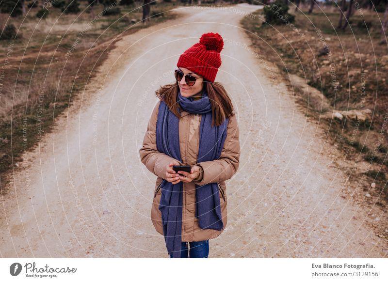 junge Backpackerin, die in der Natur wandert. Bewölkter Wintertag. Verwendung eines Mobiltelefons Abenteuer Amerikaner entdeckend Reisender grün genießen