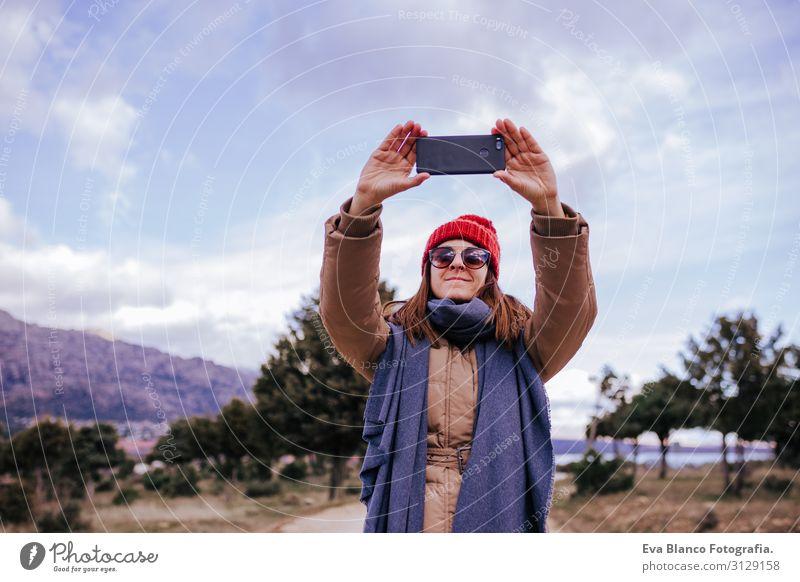 junge Backpackerin, die in der Natur wandert. Bewölkter Wintertag. Fotografieren mit dem Handy Abenteuer Amerikaner entdeckend Reisender grün genießen Westler
