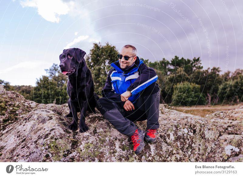 junger Wanderer am Berg mit seinem schwarzen Labrador auf dem Gipfel eines Felsens. bewölkter Wintertag Natur Unbekümmertheit gehorsam Jugendliche Glück Zunge