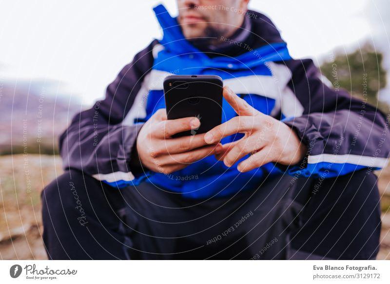 junger Wanderer mit Smartphone auf dem Gipfel des Berges. bewölkter Tag Bildschirm intelligente Uhr wandern App ultra Training Fitness Lifestyle üben Gerät