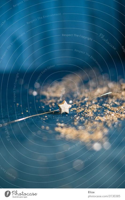 Ein goldener Stern auf blauem glitzernden Hintergrund; Weihnachten, Advent, Dekoration Weihnachten & Advent Gold Silvester u. Neujahr glänzend Stern (Symbol)