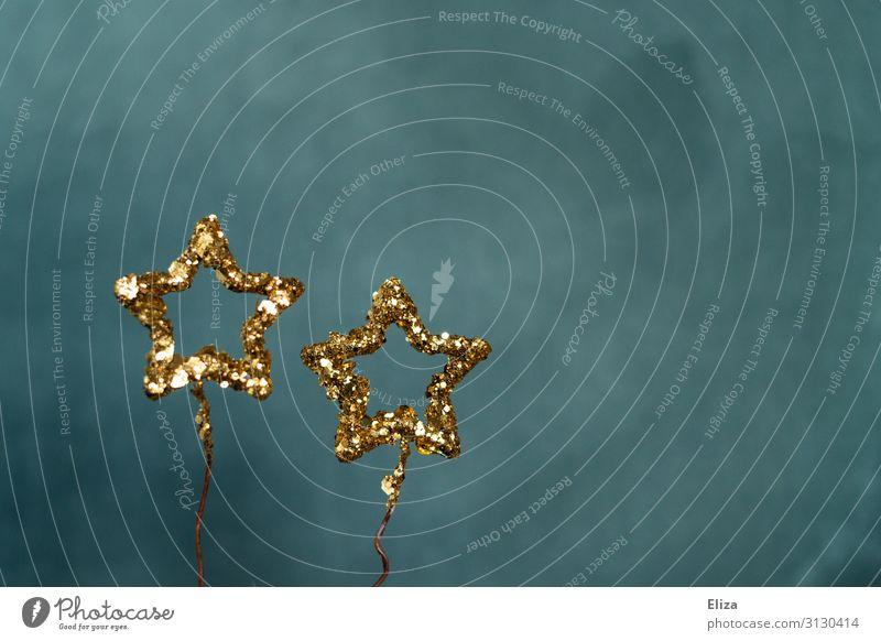 Zwei gold glitzernde Sterne vor blauem Hintergrund. Weihnachten, Advent, Dekoration. Dekoration & Verzierung Weihnachten & Advent Silvester u. Neujahr glänzend