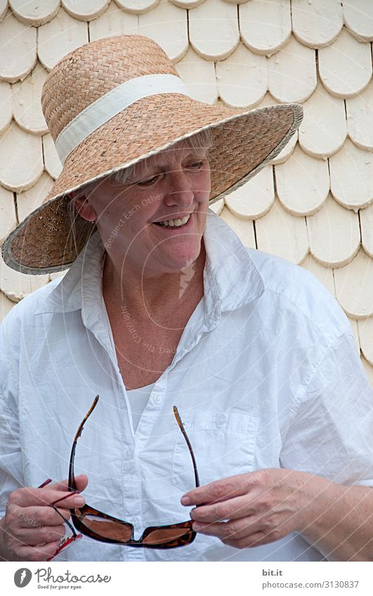Reife Frau mit Strohhut auf dem Kopf, heller, weißer Bluse und Sonnenbrille haltend in der Hand, steht im Urlauf vor einem alten Haus mit weissen Schindeln. Dame steht beim Ausflug in der Altstadt vor heller Wand und lächelt glücklich seitwärts nach unten.