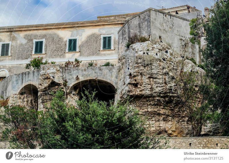 Haus auf Felsen gebaut in Sardinien Gebäude Gestein felsenfest Sedini Altbau stabil Altstadt Höhlen untergraben Architektur Fensterläden grau grün Felsvorsprung