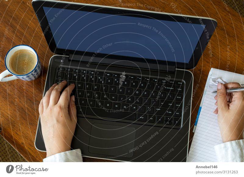 Draufsicht einer Frau, die ihren Laptop auf einem Holztisch benutzt. Kaffee Lifestyle kaufen Freizeit & Hobby Schreibtisch Tisch Arbeit & Erwerbstätigkeit
