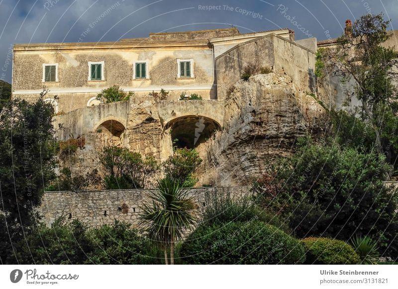 Haus auf Felsen gebaut in Sardinien in der Abendsonne Gebäude Gestein felsenfest Sedini Altbau stabil Altstadt Höhlen untergraben Architektur Fensterläden grau