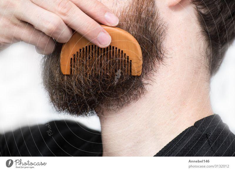 Nahaufnahme eines jungen Mannes, der seinen langen Bart mit einem Kamm gestaltet. Lifestyle Stil Haare & Frisuren Gesicht Mensch maskulin Erwachsene Mode