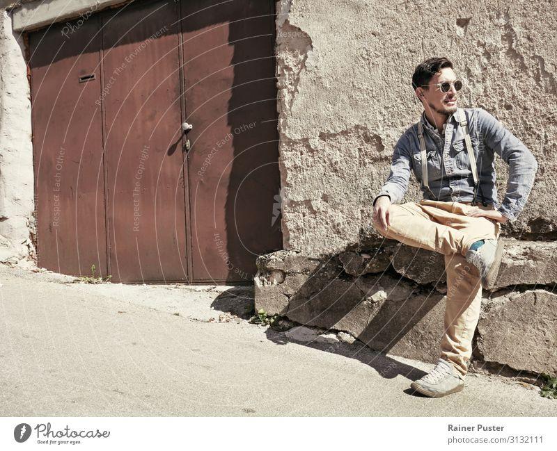 Mann mit Sonnenbrille und Hosenträgern in der Sonne Mensch Erwachsene gelb braun maskulin sitzen einzigartig Coolness Gelassenheit trendy Bart schwarzhaarig
