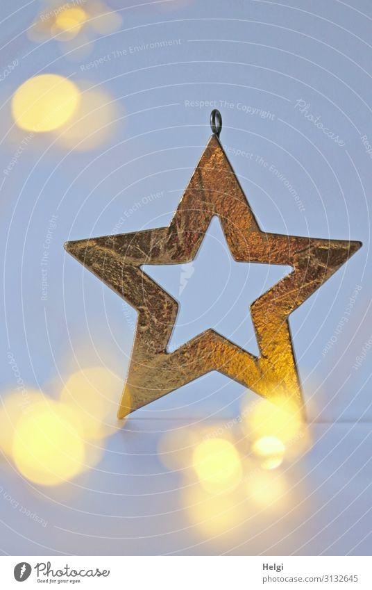 goldener Stern als Dekoration vor hellblauem Hintergrund mit leuchtendem Bokeh Weihnachten & Advent Dekoration & Verzierung Zeichen Stern (Symbol) glänzend