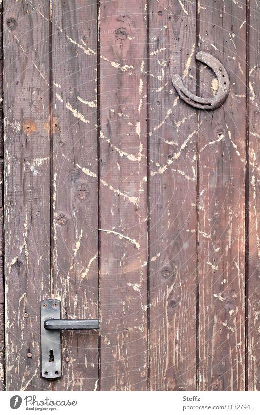 alte Zeiten mit Holz und Eisen Schutz Volksglaube Hufeisen Glück Tür Holztür Türschloss Aberglaube Rost Griff Metall Glücksbringer einfach natürlich retro braun