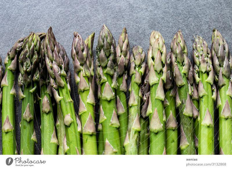 grüner Spargel auf grauer Arbeitsplatte Lebensmittel Spargelstangen Gemüse Ernährung Bioprodukte Vegetarische Ernährung Diät Frühling frisch Gesundheit lang