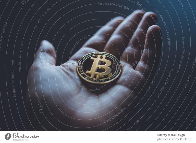 Halten einer Bitmünze Hand Finger Geldmünzen Jeton Metall Kryptowährung kaufen Investor Investition Gold Einsparungen sparen Bargeld Farbfoto Innenaufnahme