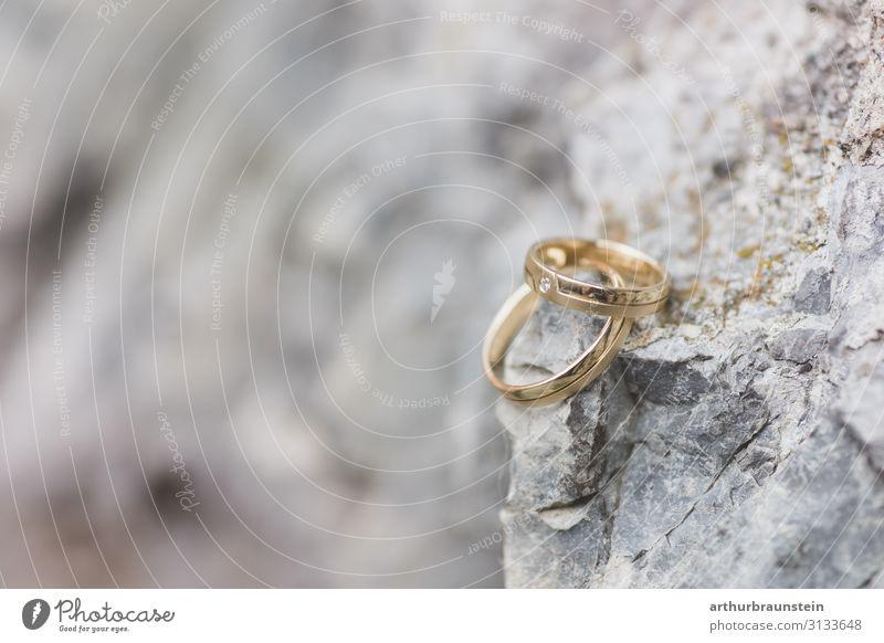 Goldene Eheringe auf einem Fels Lifestyle Glück Stein Felsen elegant Romantik kaufen Hochzeit Vertrauen Verliebtheit Ring Frühlingsgefühle steinig Heiratsantrag