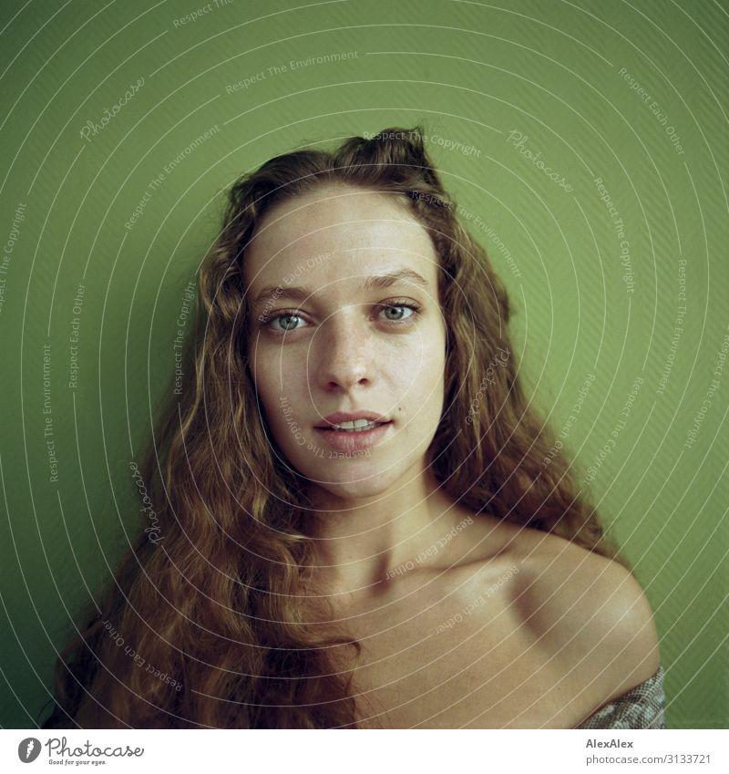 Rechteckiges Portrait einer jungen Frau vor grüner Wand Jugendliche Junge Frau Stadt schön 18-30 Jahre Gesicht Erwachsene Leben natürlich Stil außergewöhnlich