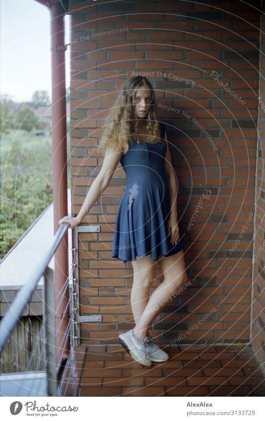 Junge Frau steht auf einem Balkon von Ziegelsteinmauer Lifestyle Stil schön Wohlgefühl Häusliches Leben Backsteinwand Geländer Jugendliche 18-30 Jahre