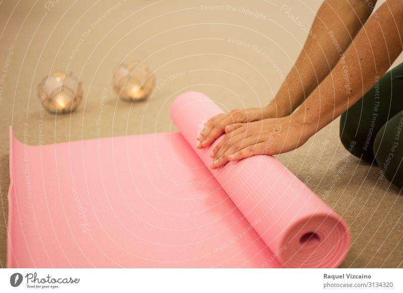 Die Hände der Frau rollen eine rosa Yogamatte auf. Lifestyle Körper Haut Gesundheitswesen Wellness Erholung Meditation Spa Massage Sport Mensch Erwachsene Hand