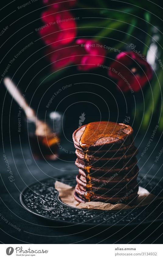 Schokoladige Pancakes mit Ahornsirup rot Foodfotografie dunkel schwarz Lebensmittel braun Ernährung süß gold Backwaren Süßwaren Dessert Frühstück