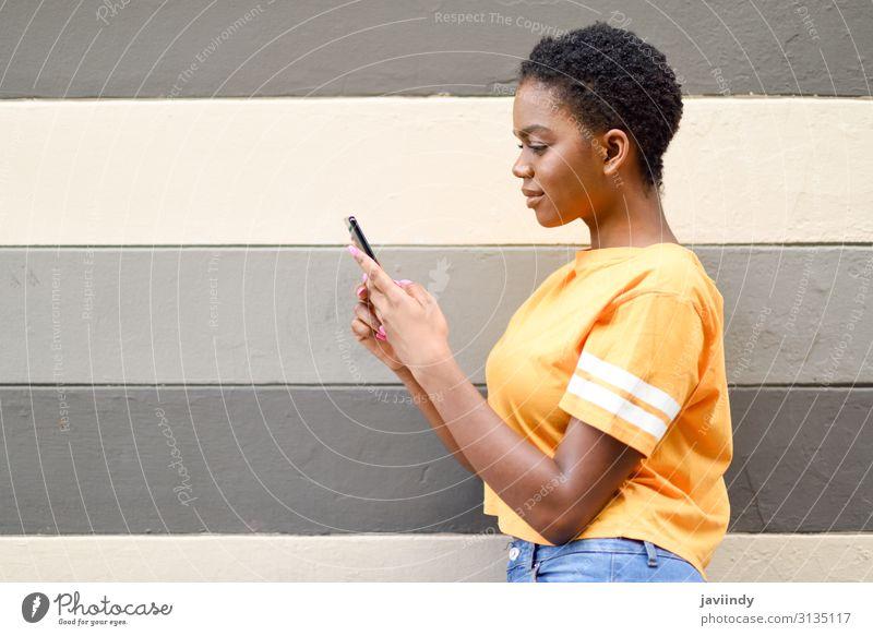 Junge schwarze Frau, die ihr Smartphone im Freien benutzt. Lifestyle Stil Glück Haare & Frisuren Telefon Handy PDA Technik & Technologie Internet Mensch feminin