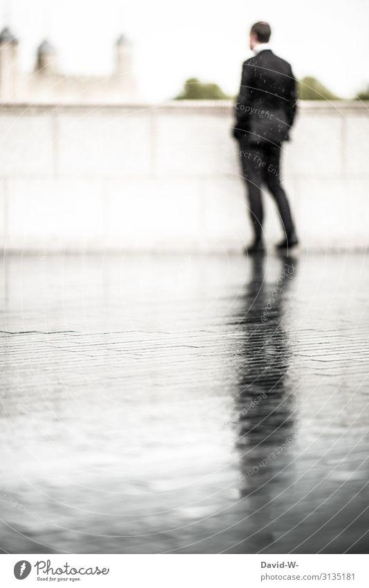 jemanden im Regen stehen lassen - Geschäftsmann steht im Regen ... auf der nassen Straße spiegelt sich sein Schatten Business businessmann Mann