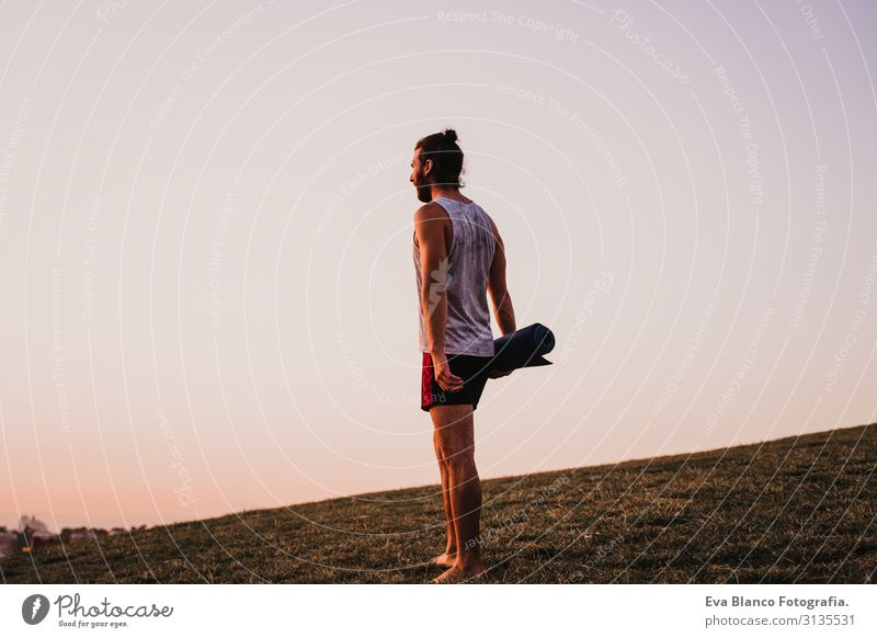junger Mann in einem Park, der bereit ist, Yogasport zu betreiben. Stadthintergrund. gesunder Lebensstil. Konzentration Posten Mensch Jugendliche Körper