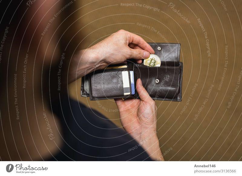 Der Mensch nimmt die goldene Bitmünze aus seiner Brieftasche, die virtuelle Währung. Geld Wirtschaft Kapitalwirtschaft Geldinstitut Business