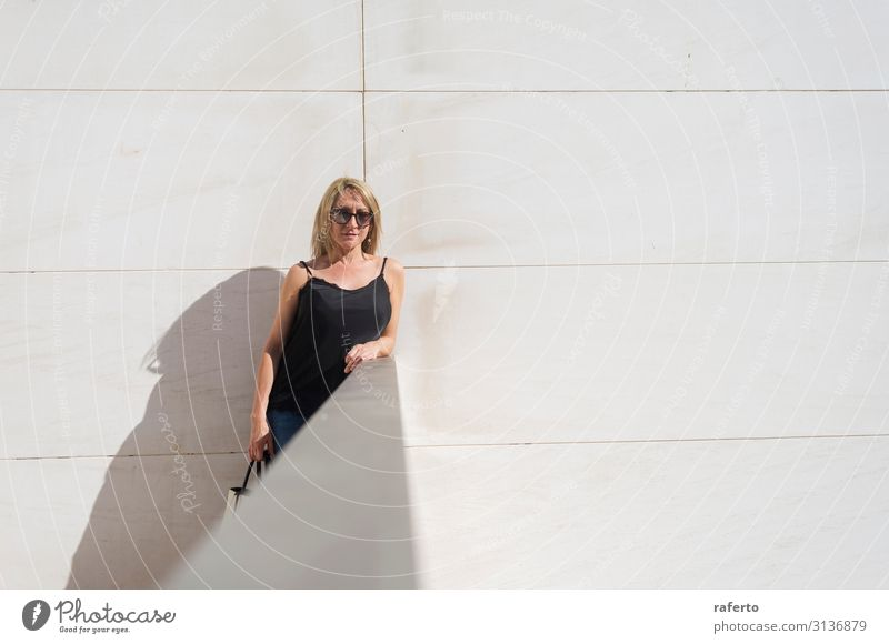 Blonde Frau, die sich an eine weiße Wand lehnt, während sie in die Kamera schaut. Lifestyle Stil Glück schön Körper Gesicht Freizeit & Hobby Sommer Mensch
