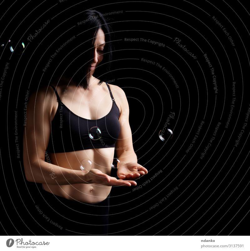 Mädchen mit einer Sportfigur hält eine Seifenblase. Lifestyle schön Körper Gesicht Mensch Frau Erwachsene Hand Bekleidung Fitness stehen sportlich dunkel dünn