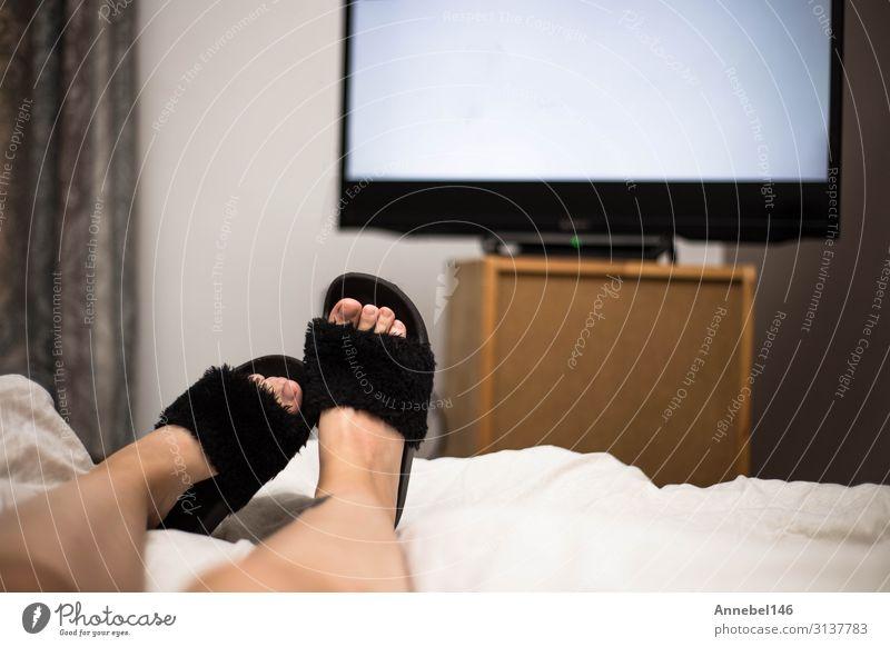 Der Mensch sieht nachts im Bett mit schwarzen Flip Flops fern. Getränk Freude Erholung Freizeit & Hobby Sofa Tisch Schlafzimmer Entertainment Bildschirm