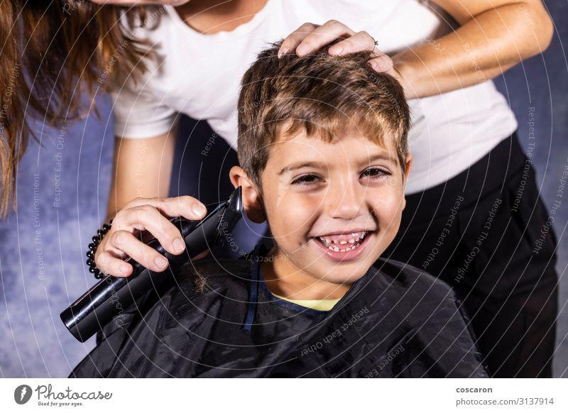 Kleiner Junge lässt sich mit einer Schneidemaschine die Haare schneiden. Lifestyle kaufen Stil schön Haare & Frisuren Gesicht Spielen Kind Beruf Friseur