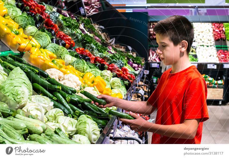 Kind wählt Gemüse im Regal im Supermarkt aus. Lebensmittel Vegetarische Ernährung kaufen Marktplatz stehen frisch natürlich Käufer auswählend Teenager