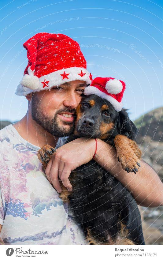 Mann und sein Hund mit Weihnachtsmützen. Freude Winter Weihnachten & Advent Erwachsene Freundschaft 1 Mensch 30-45 Jahre Tier Hut Haustier Liebe niedlich blau