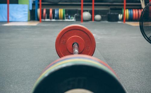 Langhantel mit Gewichten in einem Fitnessstudio Ball Metall Curl-Hantel Hantelscheiben Gewichtheben Bar Sporthalle Sportgeräte Bodybuilding üben Kasten bügeln