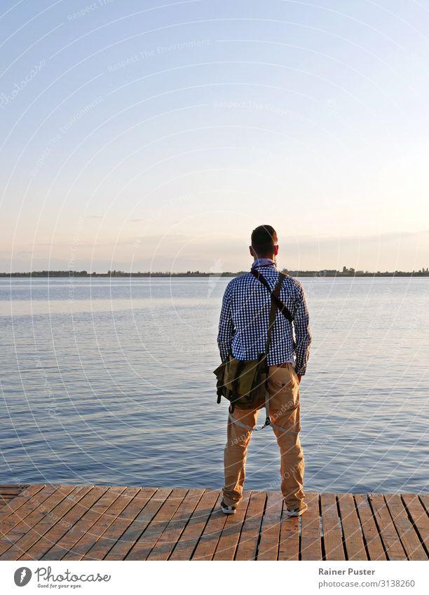 Mann mit Tasche und Kamera auf einem Steg blau ruhig Ferne Erwachsene Stil See orange maskulin frei Idylle stehen einzigartig Seeufer Wolkenloser Himmel
