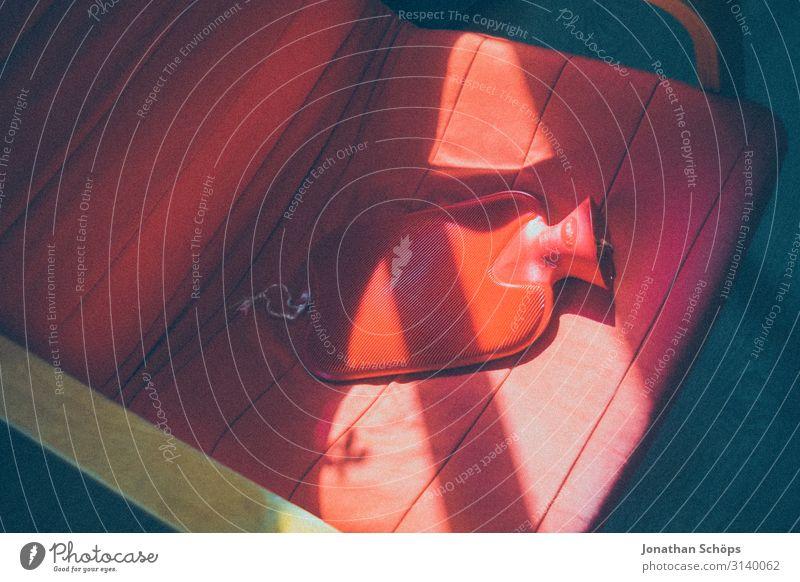 rote Wärmflasche auf rotem Sessel Gesundheit Krankenpflege Krankheit harmonisch Wohlgefühl Erholung ruhig ästhetisch frieren Erkältung Wärme heiß Bauchschmerzen