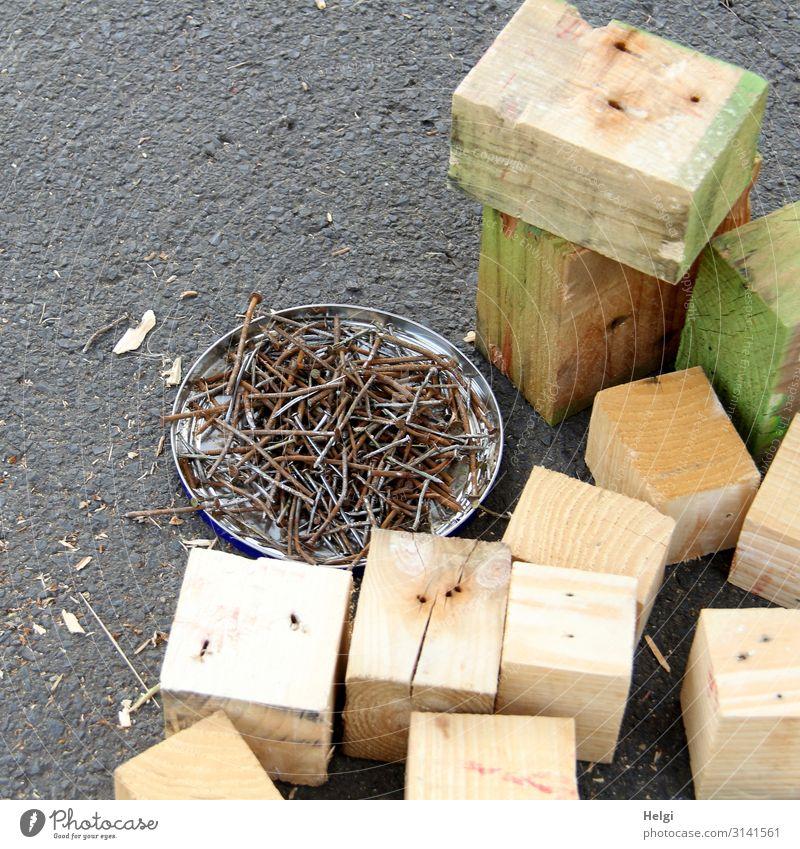 Holzklötze und viele alte Nägel  liegen auf Asphalt Metall Arbeit & Erwerbstätigkeit stehen authentisch eckig braun grau grün Tatkraft Beginn anstrengen
