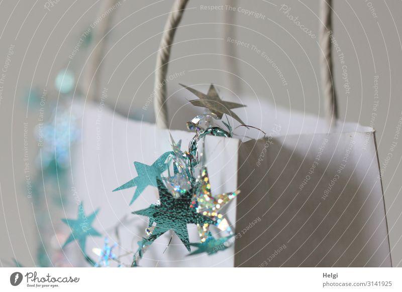 türkise und silberne Sterne hängen an als Dekoration an einer weißen Papiertasche Feste & Feiern Weihnachten & Advent Dekoration & Verzierung Tüte