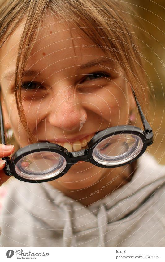 Lachendes, fröhliches Mädchen zieht dicke Hornbrille; Scherzartikel mit hoher Dioptrin aus Spaß, Verkleidung und Freude, an Karneval; Fasching an und lacht dabei fröhlich in die Kamera.